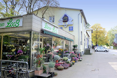 Marienthal ist ein Hamburger Stadtteil im Bezirk Hamburg Wandsbek. Flachbau  mit  gelben Kacheln als Fassade - Blumenladen am Wandsbeker Bahnhof, im Hintergrund das Bahnhofsgebäude.
