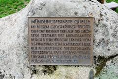 Quelle der Breg in Furtwangen - Schwarzwald in Baden-Württemberg; Hauptquellfluss der Donau, hydrologische Donauquelle. Metalltafel an einem Findling mit der Aufschrift: Mündungsfernste Quelle; an diesem geographisch wichtigen Ort beginnt der der Lau