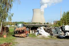 Grundremmingen, Gemeinde an der Donau in Bayern - Stadtort des gleichnamigen Kernkraftwerks, Siedewasserreaktors. Bauernhof mit Traktor, dahinter die Kühltürme vom AKW.