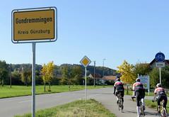 Grundremmingen, Gemeinde an der Donau in Bayern - Stadtort des gleichnamigen Kernkraftwerks, Siedewasserreaktors. Ortsschild Grundremmingen, Kreis Günzburg - Rennradfahrer in Fahrt.