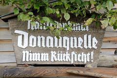 Quelle der Breg in Furtwangen - Schwarzwald in Baden-Württemberg; Hauptquellfluss der Donau, hydrologische Donauquelle. Geschnitztes Holzschild mit der Inschrift Naturdenkmal Donauquelle, nimm Rücksicht!