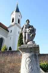 Grundremmingen, Gemeinde an der Donau in Bayern - Stadtort des gleichnamigen Kernkraftwerks, Siedewasserreaktors. Kriegerdenkmal vor der St. Martinskirche - Steinfiguren mit sterbendem Soldaten.