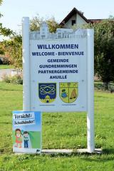 Grundremmingen, Gemeinde an der Donau in Bayern - Stadtort des gleichnamigen Kernkraftwerks, Siedewasserreaktors. Willkommensschild am Ortseingang, Wappen mit Atomsybol.