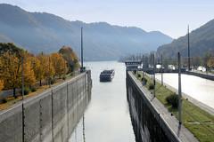 Kraftwerk Jochenstein - Laufkraftwerk in der Donau, deutsch-österreichische Grenze in der Nähe von Passau. Das 109 m lange Kreuzfahrtschiff  THE A  fährt in die Kraftwerkschleuse ein; das 1993 gebaute Schiff hat Kabinen für 146 Passagiere.