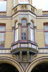Bilder aus der Hamburger Innenstadt - Stadtteil Neustadt. Hausfassade mit gelben Backstein - Erker mit Säulen und farbigem Blattwerk in den Colonnaden.