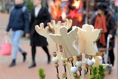 Fotos aus dem Hamburger Stadtteil Niendorf, Bezirk Eimsbüttel. Weihnachtsmarkt am Tibarg, der Einkaufsstraße Niendorfs - Stand mit  Holzengeln, im Hintergrund MarktbesucherInnen.