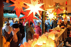 Weihnachtsmärkte in der Innenstadt - Altstadt von Hamburg. Verkaufsstand mit beleuchteten Weihnachtssternen auf dem Hamburger Rathausmarkt.