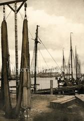 Alte Fotografie vom Hochseefischereihafen in Cuxhaven - Netze sind zum Trocknen aufgehängt, Fischereiboote / Kutter liegen im Hafen.