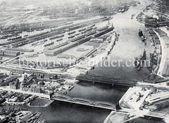 Historische Luftaufnahme von der Norderelbe mit den Elbbrücken - Blick auf den Veddeler Marktplatz, Mündung des Marktkanals. Im Hintergrund die Hafenbecken vom Kleinen Grasbrook - Moldauhafen, Segelschiffhafen und Hansahafen.