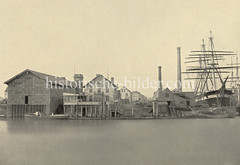 Historische Fotografie vom Reiherstieg in Hamburg Steinwerder - Werft mit Segelschiff, Schornsteine und Lagerhäuser.