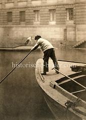 Ein Ewerführer steht am Bug einer Schute und stakt das Transportschiff durch einen Hamburger Fleet.