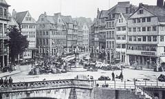 Historische Bilder vom Messberg in der Hamburger Altstadt, Innenstadt. Der Marktplatz am Messberg ca. 1880; in der Bildmitte der Vierländer Brunnen und einige Marktstände. Im Vordergrund lks. das steinerne Geländer der Wandrahmsbrücke.