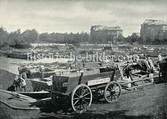 Historische Fotografie von der Hohenfelder Bucht im Stadtteil Hamburg Hohenfelde. Pferdefuhrwerke stehen am Ufer der Bucht - auf dem Wasser div. Lastkähne und Schuten.