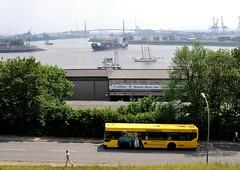 """Blick von der Rainvilleterrasse auf die Kaistrasse und die Elbe. Am Ufer ein Schuppen """"Fischmarkt - Hamburg Altona GmbH. Vom Köhlbrand kommt ein Containerfeeder und biegt in die Elbe ein - ein Segelschiff fährt elbabwärts. Im Hintergrund die Köhlbran"""