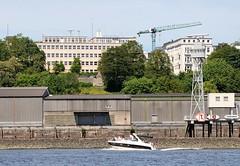 Lagerschuppen an der Elbe - Seefahrtschule Rainvilleterrasse. Ein Sportboot fährt auf der Elbe vor der Altonaer Kaianlage.