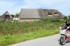 Neuengamme  ist ein Hamburger Stadtteil im Elbmarsch-Gebiet der Vierlande im Bezirk Bergedorf. Reetgedecktes Wohnwirtschaftsgebäude mit Dachfenstern, Motorradfahrer.