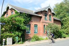 Neuengamme  ist ein Hamburger Stadtteil im Elbmarsch-Gebiet der Vierlande im Bezirk Bergedorf. Wohnhaus mit Ziergiebel, Schnitzwerk am Neuengammer Hausdeich, Rennradfahrer.