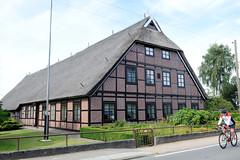 Neuengamme  ist ein Hamburger Stadtteil im Elbmarsch-Gebiet der Vierlande im Bezirk Bergedorf. Hofanlage, restauriertes Fachwerkgebäude mit Reetdach im Neuengammer Hausdeich, Rennradfahrer.