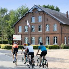 Neuengamme  ist ein Hamburger Stadtteil im Elbmarsch-Gebiet der Vierlande im Bezirk Bergedorf. Historisches Wohnwirtschaftsgebäude am Neuengammer Hausdeich - errichtet 1890 steht das Haus unter Denkmalschutz; Rennradfahrer auf der Straße.