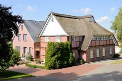 Fotos aus dem Hamburger Stadtteil Reitbrook, Bezirk Bergedorf. Wohnhaus mit Reetdach und Fachwerk, daneben Neubau am Vorderdeich.