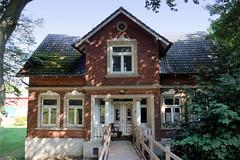 Fotos aus dem Hamburger Stadtteil   Allermöhe, Bezirk Hamburg Bergedorf; Wohnhaus am Allermöher Deich - Tür mit Schnitzwerk, Eingang mit Säulen.
