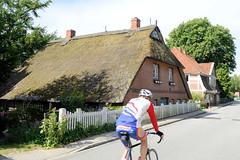 Neuengamme  ist ein Hamburger Stadtteil im Elbmarsch-Gebiet der Vierlande im Bezirk Bergedorf. Reetgedeckte Kate aus dem 18. Jh.  im Neuengammer Hausdeich - ein Radrennfahrer fährt auf einer Tour durch die Vierlande.