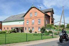 Neuengamme  ist ein Hamburger Stadtteil im Elbmarsch-Gebiet der Vierlande im Bezirk Bergedorf. Denkmalgeschütztes Wohnwirtschaftsgebäude im Neuengammer Hausdeich, Motorradfahrer.