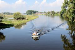 Fotos aus dem Hamburger Stadtteil   Allermöhe, Bezirk Hamburg Bergedorf. Blick von der Allermöher Kirchenbrücke auf die Dove-Elbe; ein Motorboot fährt langsam auf dem Fluss.
