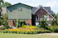 Fotos aus dem Hamburger Stadtteil Ochensenwerder, Bezirk Bergedorf. Blumengarten, alte Scheune mit Holzfassade.