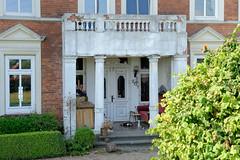Fotos aus dem Hamburger Stadtteil Reitbrook, Bezirk Bergedorf. Eingang mit Säulen und Balkon, denkmalgeschütztes Wohnwirtschaftsgebäude am Vorderdeich, errichtet um 1890.
