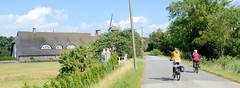 Fotos aus dem Hamburger Stadtteil Reitbrook, Bezirk Bergedorf. Reedachgebäude / Wohnwirtschafthaus, im Hintergrund die Reitbrooker Mühle - Radfahrerinnen.