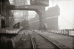 Unter den Portalen der Halbportalkräne steht ein Güterzug an der Rampe - Kaiarbeiter / Frachtschiff; ca. 1934.