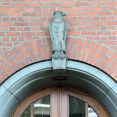 Fotos aus dem Hamburger Stadtteil Neugraben-Fischbek, Bezirk Hamburg Harburg. Eingang mit Adlerskulptur - ehem. Apothekergebäude in der Cuxhavener Straße, errichet 1951 - Architekt Johannes Stahmann; das jetzige Wohnhaus steht unter Denkmalschutz.