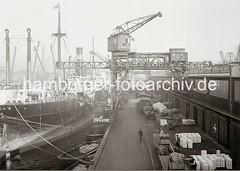 Abgebäumter Frachter am Kai - Pferdefuhrwerke und Güterwaggons an der Laderampe; ca. 1934.