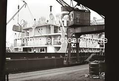 Kisten im Ladegeschirr des Halbportalkrans; Frachtschiff am Hafenkai; ca. 1934.