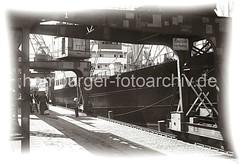 Arbeit im Hamburger Hafen - Halbportalkrane, Frachter an der Kaimauer; Hafenarbeiter beim Kistentransport; ca. 1934.