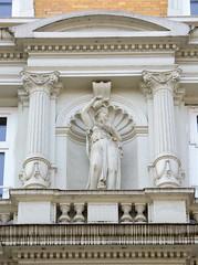 Historische Architektur in der Hamburger Innenstadt, Stadtteil Neustadt.  Figürlicher Bauschmuck zwischen Säulen - Hausfassade in den Colonnaden, 1878.