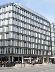 Architektur in der Hamburger Innenstadt, Stadtteil Neustadt. Modernes Bürogebäude mit Straßenrestaurant in der Hamburger Innenstadt / Dammtorstraße.