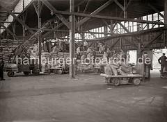 Elektrokarren mit Säcken im Kaischuppen - Schuppenlaufkran; Hafenarbeiter auf gestapelten Säcken; ca. 1934.