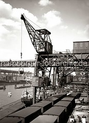 Dreifachkran beim Löschen eines Frachters - Güterzüge am Kai; ca. 1934.