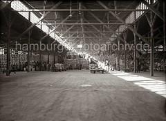 Hafenarbeiter stapeln Säcke im Kaischuppen - Elektrokarren transportieren Ladung; ca. 1934.