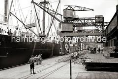 Beladen eines Frachtschiffs - Gleisarbeiten auf dem Hafenkai; ca. 1934.
