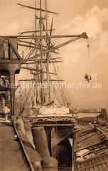 Historische Hafenszene Hamburg Altona - Frachtsegler Olaf Kyrre mit dem norwegischen Heimathafen Langesund. Am Haken des Hafenkrans hängt eine Ladung Säcke; im Vordergrund ein Lastkahn.