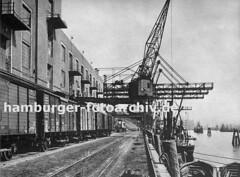 Güterwaggons und Halbportalkräne vor dem Altonaer Kaispeicher. Am Kai des Altonaer Hafens liegen Frachtschiffe und Schuten; die Streichdalben ragen über die Kaimauer.