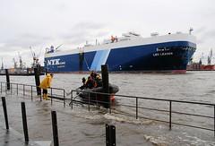 Schlauchboot am überfluteten Hafenkai im Altonaer Hafen. Ein Frachtschiff RoRo-Schiff verlässt den Hamburger Hafen.