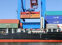 Zwei Container werdern mit der Laufkatze aus dem Laderaum des Feederschiffs gehoben und an Land gebracht.