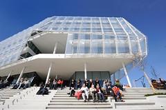 Besucher des modernen Hamburger Stadtteils sitzen auf den Stufen in der Sonne und blicken auf die Elbe.