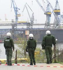 Polizisten mit Helm und im Kampfanzug stehen an der Hafentreppe.
