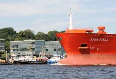 Schiffsbug auf der Elbe vor Hamburg Neumühlen. Der knapp 150m lange Tanker läuft aus dem Hamburger Hafen aus - im Hintergrund die Hafenschlepper an ihrem Liegeplatz und Büroarchitektur an der Strasse Neumühlen.