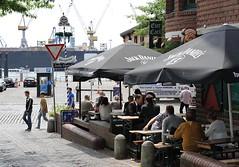 Restaurant mit Tischen am Fischmarkt, Grosse Elbstrasse. Auf der gegenüber liegenden Elbseite die Werftanlagen der Hamburger Werft Blohm & Voss.